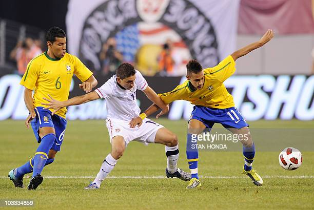 Neymar and Andre Santos of Brazil with Alejandro Bedoya of the US during a friendly match August 10, 2010 at New Meadowlands Stadium in East...