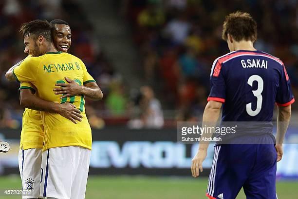 Neymar and Robinho of Brazil shares a hug as Gotoku Sakai of Japan walks away dejected at the end of the match Japan during the international...