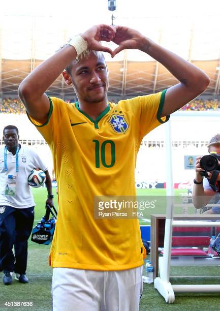 Neymar celebrates the win as he walks off the pitch after the 2014 FIFA World Cup Brazil Round of 16 match between Brazil and Chile at Estadio...