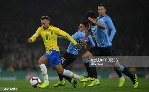 Neymar da Silva Santos Jœnior of Brazil is tackled by Lucas Torreira and Bruno MŽndez of Uruguay during the International Friendly between Brazil and...