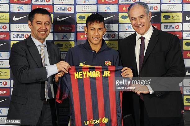 Neymar holds his new jersey with the FC Barcelona VicePresident Josep Maria Bartomeu and FC Barcelona Sport Director Andoni Zubizarreta during the...