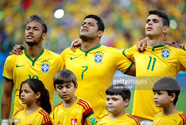 Neymar, Hulk and Oscar of Brazil sing the National Anthem prior to the 2014 FIFA World Cup Brazil Quarter Final match between Brazil and Colombia at...