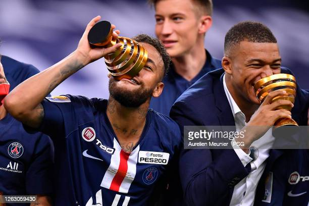 Neymar Jr and Kylian Mbappe of Paris Saint-Germain raise the Trophy after winning the French League Cup final match against Olympique Lyonnais after...