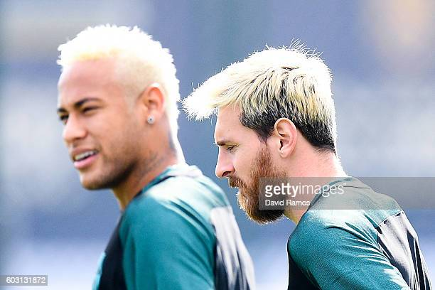 Neymar Jr and Lionel Messi of FC Barcelona look on during a training session ahead of their UEFA Champions League Group C match against Celtic FC at...