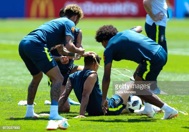 Neymar Jr and Willian of Brazil smash eggs on Philippe Coutinho of Brazil as a birthday prank during a Brazil training session ahead of the FIFA...