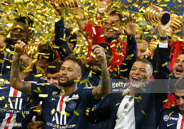 Neymar Jr, Kylian Mbappe of PSG and teammates celebrate the victory during the trophy ceremony following the French League Cup final between Paris...