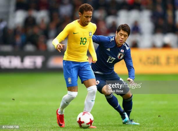 Neymar Jr of Brazil and Hiroki Sakai of Japan battle for possession during the international friendly match between Brazil and Japan at Stade...