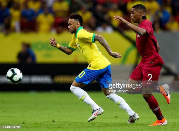 Neymar Jr of Brazil and RóRó of Qatar compete for the ball during the International Friendly Match between Brazil and Qatar at Mane Garrincha Stadium...