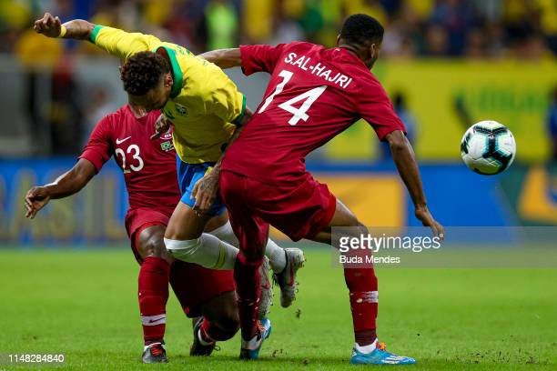 Neymar Jr of Brazil competes for the ball with Assim Madibo and Salem AlHajri of Qatar during the International Friendly Match between Brazil and...