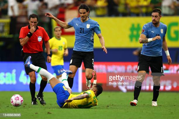 Neymar Jr. Of Brazil falls down as he fights for the ball with Edinson Cavani and Sebastian Coates of Uruguay during a match between Brazil and...
