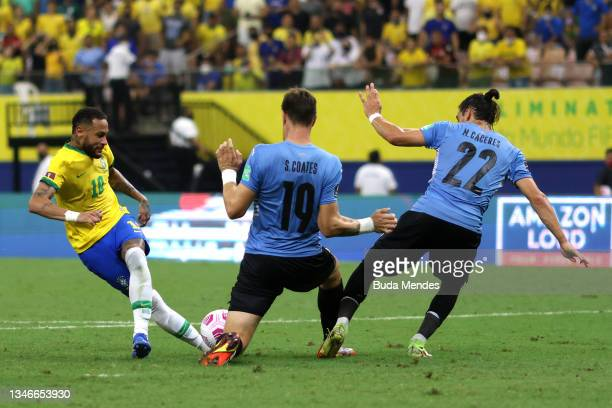 Neymar Jr. Of Brazil fights for the ball with Sebastian Coates and Joaquin Piquerez Moreira of Uruguay during a match between Brazil and Uruguay as...