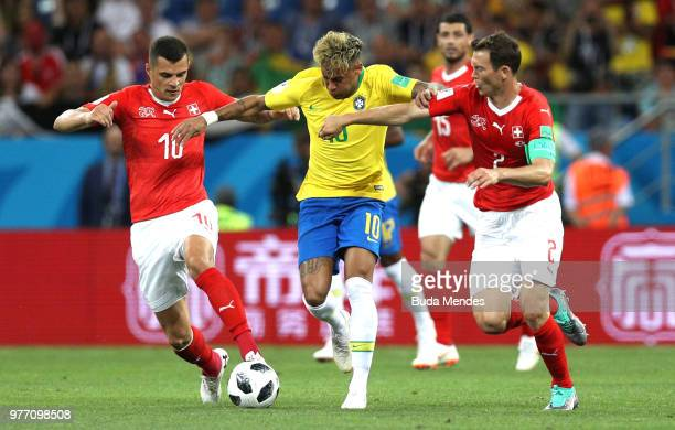 Neymar Jr of Brazil is challenged by Granit Xhaka of Switzerland and Stephan Lichtsteiner of Switzerland during the 2018 FIFA World Cup Russia group...