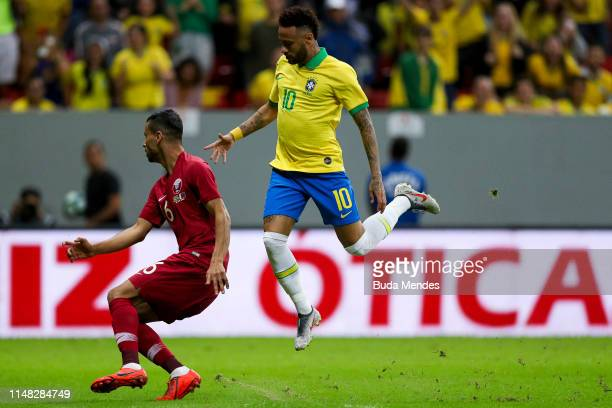 Neymar Jr of Brazil jumps as he compete with Boualem Khoukhi during the International Friendly Match between Brazil and Qatar at Mane Garrincha...