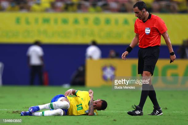 Neymar Jr. Of Brazil reacts after suffering an injury as Referee Fernando Rapallini gestures during a match between Brazil and Uruguay as part of...