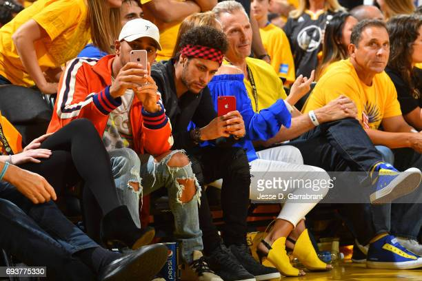 Neymar Jr of FC Barcelona and Racecar Driver Lewis Hamilton take photos during Game Two of the 2017 NBA Finals between the Cleveland Cavaliers and...
