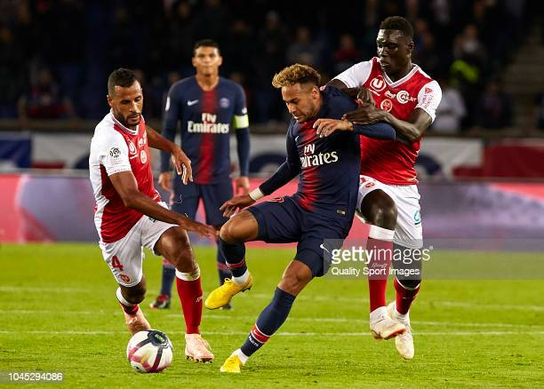 Neymar Jr of Paris Saint Germain competes for the ball with JacquesAlaixys Romao and Aly Ndom of Stade Reims during the French Ligue 1 match between...