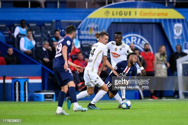 Neymar Jr of Paris SaintGermain is tackled during the Ligue 1 match between Paris SaintGermain and Angers SCO at Parc des Princes on October 05 2019...