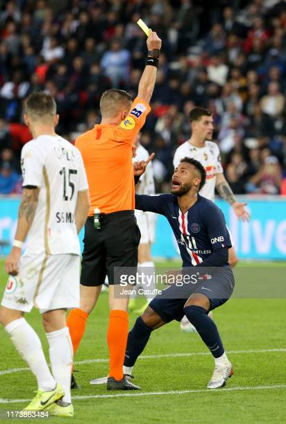 Neymar Jr of PSG receives a yellow card from referee Willy Delajod during the Ligue 1 match between Paris SaintGermain PSG and SCO Angers at Parc des...
