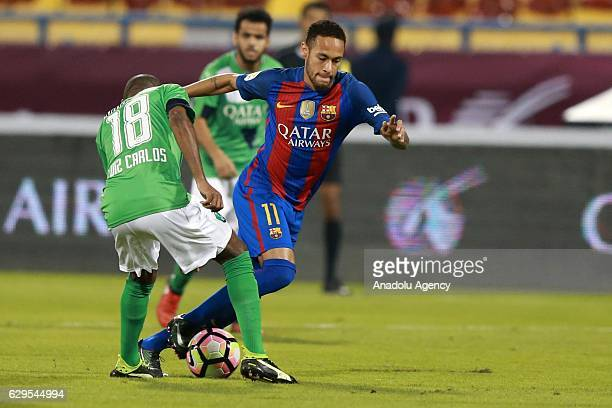 Neymar of Barcelona in action against Luiz Carlos during a friendly soccer match between Al-Ahli Saudi and Barcelona at Al-Gharrafa Stadium in Doha,...