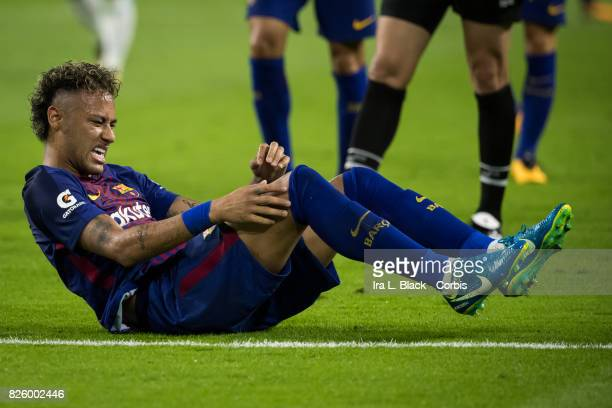 Neymar of Barcelona shows the pain from another hit during the International Champions Cup El Clásico match between FC Barcelona and Real Madrid at...