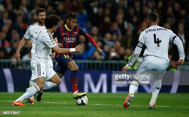 Neymar of Barcelona takes on Pepe and Sergio Ramos of Real Madrid during the La Liga match between Real Madrid CF and FC Barcelona at the Bernabeu on...