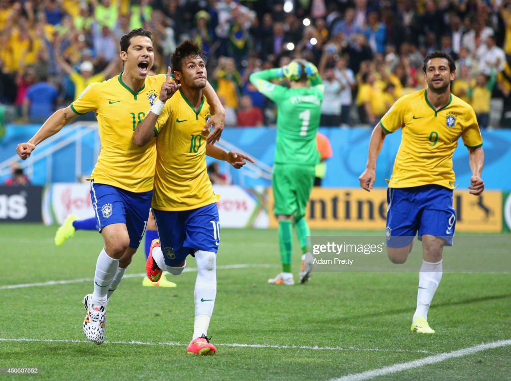 Neymar of Brazil (C) celebrates his second goal with Hernanes in the second half during the 2014 FIFA World Cup Brazil Group A match between Brazil and Croatia at Arena de Sao Paulo on June 12, 2014 in Sao Paulo, Brazil.