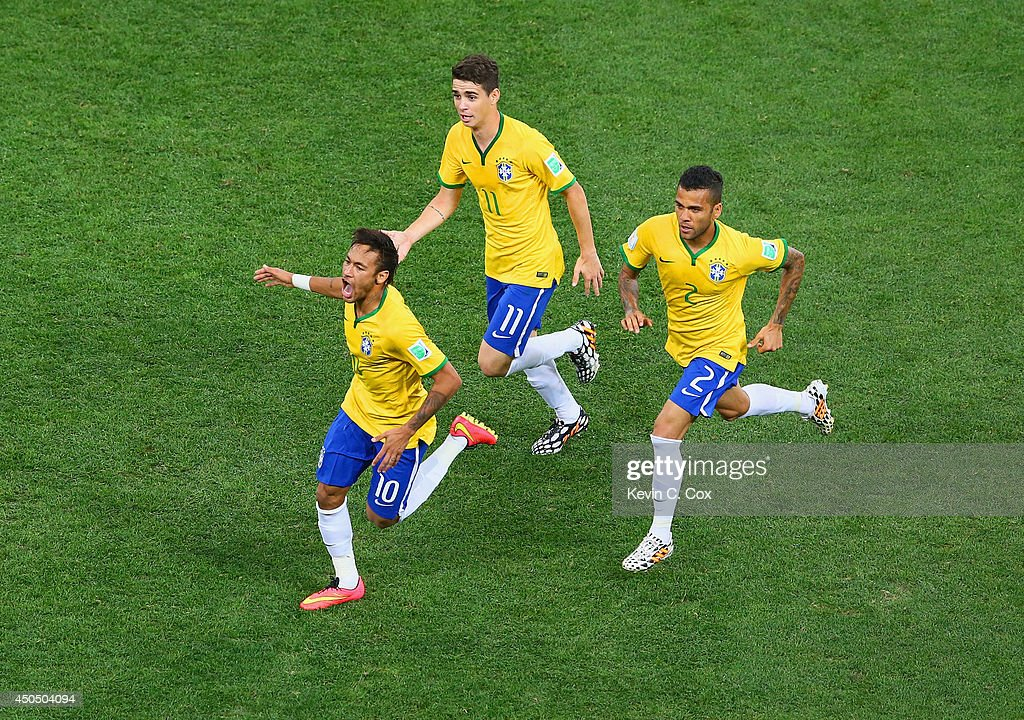 Neymar of Brazil (L) celebrates scoring a first half goal with Oscar and Dani Alves during the 2014 FIFA World Cup Brazil Group A match between Brazil and Croatia at Arena de Sao Paulo on June 12, 2014 in Sao Paulo, Brazil.