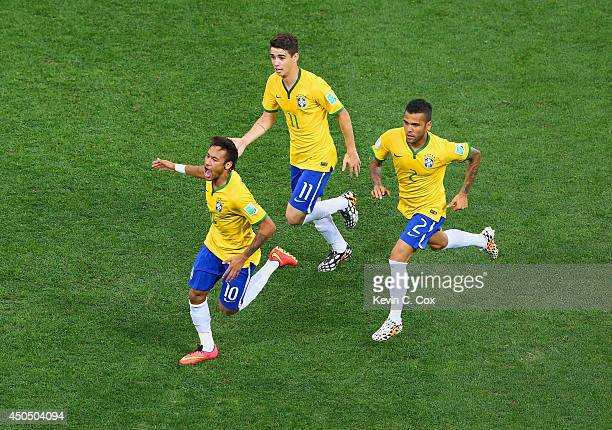 Neymar of Brazil celebrates scoring a first half goal with Oscar and Dani Alves during the 2014 FIFA World Cup Brazil Group A match between Brazil...