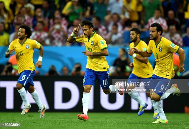 Neymar of Brazil celebrates wih team-mates after scoring the equalizing goal during the 2014 FIFA World Cup Brazil Group A match between Brazil and...