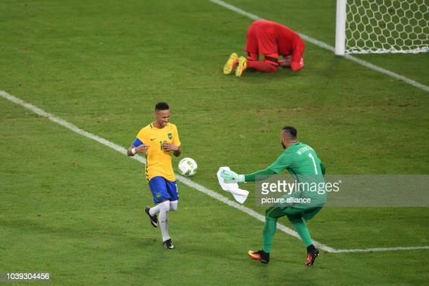 Neymar of Brazil celebrates with Brazilian goalkeeper Weverton as goalkeeper Timo Horn of Germany lies on the ground after Neymar shot the winning...