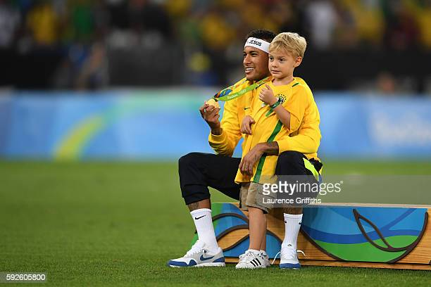 Neymar of Brazil celebrates with his son after the Men's Football Final between Brazil and Germany at the Maracana Stadium on Day 15 of the Rio 2016...
