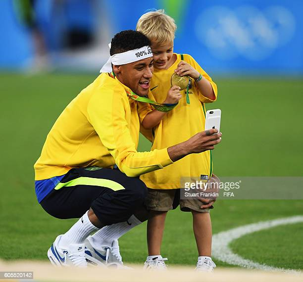 Neymar of Brazil celebrates with his son at the Olympic Men's Final Football match between Brazil and Germany at Maracana Stadium on August 20 2016...
