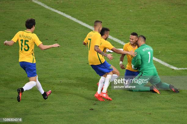Neymar of Brazil celebrates with teammates after he shot the winning goal in the penalty shoot-out during the Men's soccer Gold Medal Match between...