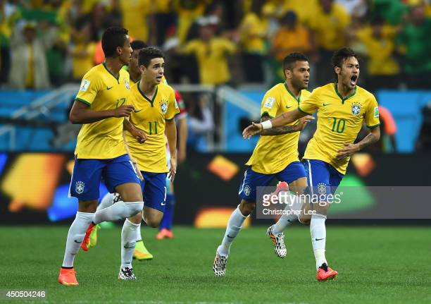 Neymar of Brazil celebrates with teammates after scoring a first half goal during the 2014 FIFA World Cup Brazil Group A match between Brazil and...