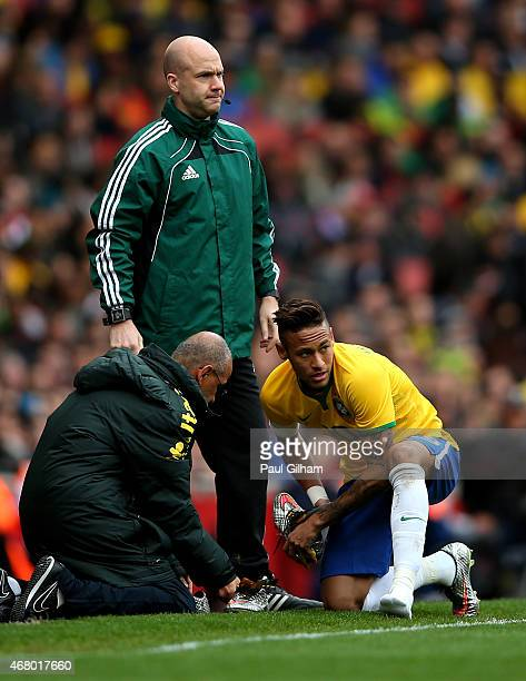 Neymar of Brazil changes his boots during the international friendly match between Brazil and Chile at the Emirates Stadium on March 29 2015 in...