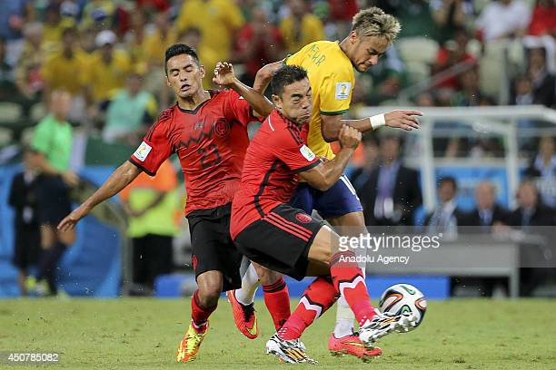 Neymar of Brazil clashes with Mexico's Fabian at World Cup match between Brazil and Mexico in the Estádio Castelão World Cup stadium in Fortaleza...