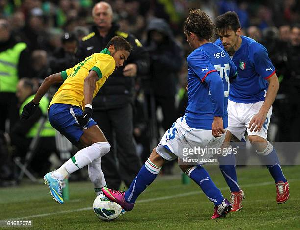 Neymar of Brazil competes for the ball with Alessio Cerci and Christian Maggio of Italy during the international friendly match between Italy and...