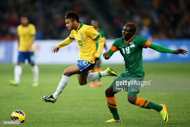 Neymar of Brazil competes the ball with Chongo Kabaso of Zambia during the international friendly match between Brazil and Zambia at Beijing National...