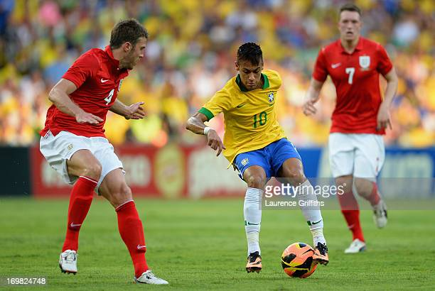 Neymar of Brazil competes with Michael Carrick of England during the International Friendly match between Brazil and England at the Maracana Stadium...