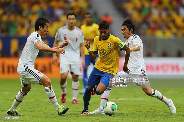 Neymar of Brazil competes with Yasuhito Endo and Makoto Hasebe of Japan during the FIFA Confederations Cup Brazil 2013 Group A match between Brazil...