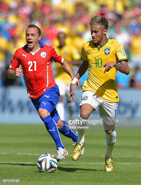 Neymar of Brazil controls the ball as Marcelo Diaz of Chile gives chase during the 2014 FIFA World Cup Brazil round of 16 match between Brazil and...