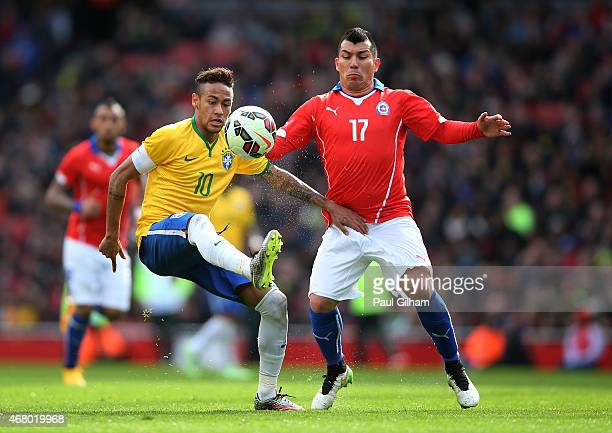 Neymar of Brazil controls the ball under pressure from Gary Medel of Chile during the international friendly match between Brazil and Chile at the...