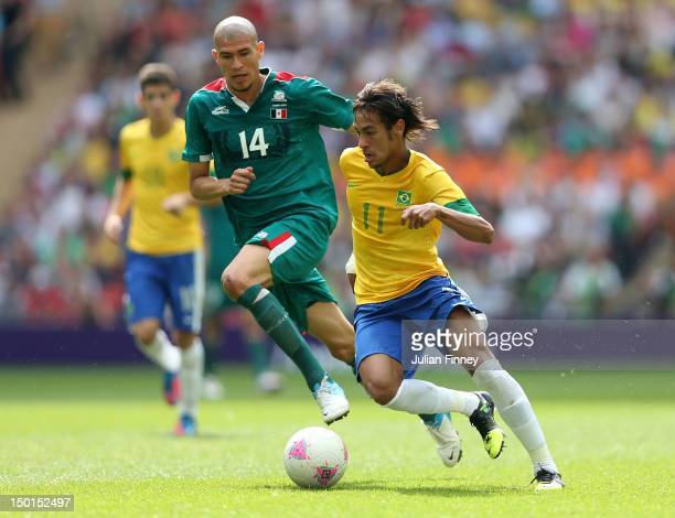 Neymar of Brazil controls the ball under pressure from Jorge Enriquez of Mexico during the Men's Football Final between Brazil and Mexico on Day 15...