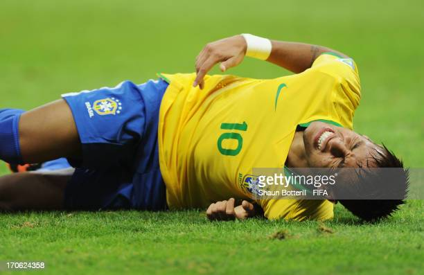 Neymar of Brazil grimaces in pain during the FIFA Confederations Cup Brazil 2013 Group A match between Brazil and Japan at National Stadium on June...