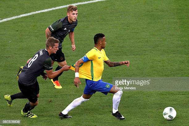 Neymar of Brazil has his shirt pulled by Lars Bender of Germany during the Men's Football Final between Brazil and Germany at the Maracana Stadium on...