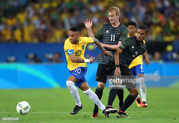 Neymar of Brazil holds off Julian Brandt of Germany and Jeremy Toljan of Germany during the Men's Football Final between Brazil and Germany at the...