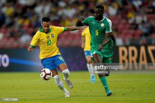 Neymar of Brazil holds off Salif Sane of Senegal during the international friendly match between Brazil and Senegal at the Singapore National Stadium...