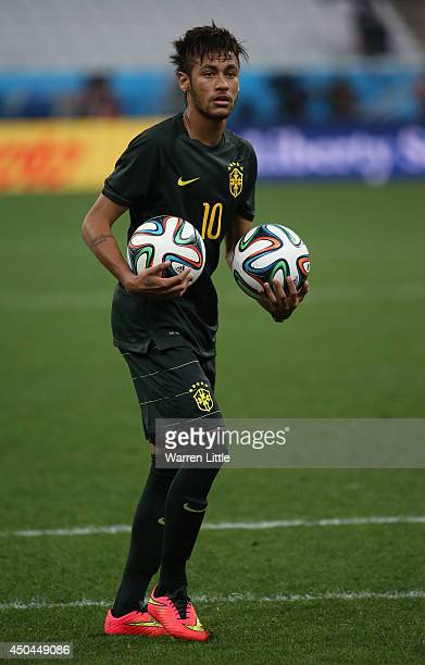 Neymar of Brazil holds two Adidas 'Brazuca' balls during a Brazil training session ahead of the 2014 FIFA World Cup Brazil opening match against...