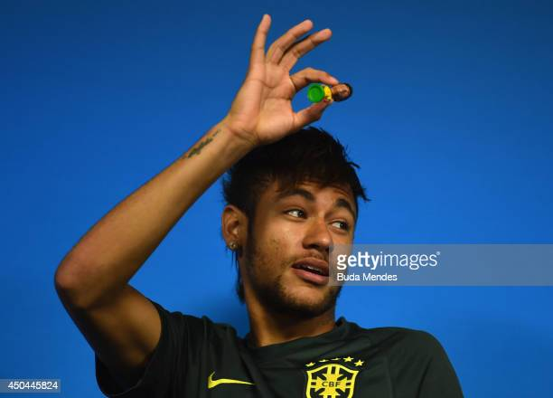 Neymar of Brazil holds up a figurine during a Brazil press conference ahead of the 2014 FIFA World Cup Brazil opening match against Croatia at Arena...