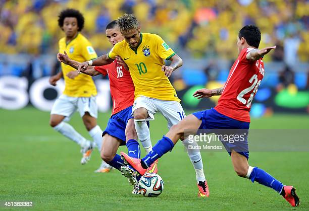 Neymar of Brazil is challenged by Felipe Gutierrez and Charles Aranguiz of Chile during the 2014 FIFA World Cup Brazil round of 16 match between...